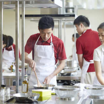 students-preparing-their-dishes-in-the-culinary-lab